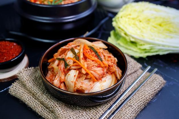 Mangiare kimchi cavolo e riso in una ciotola nera con le bacchette. Foto Premium