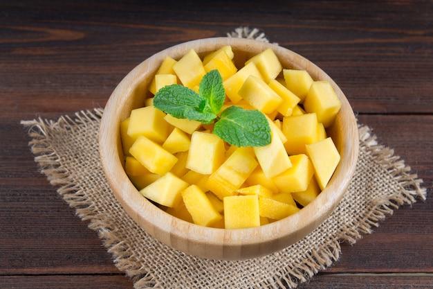 Mango della frutta tropicale in un piatto su un fondo di legno, intero o affettato. Foto Premium