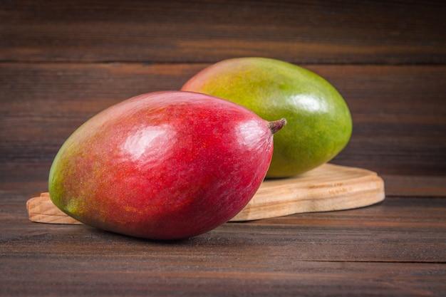 Mango della frutta tropicale su un fondo di legno, intero o affettato. Foto Premium