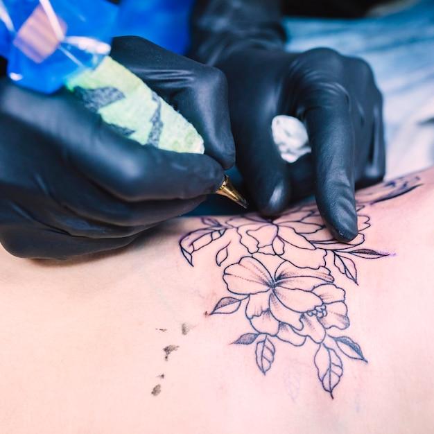 Mani che fanno il tatuaggio del fiore con l'ago Foto Gratuite