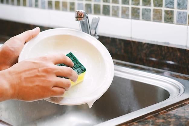 Mani che lavano i piatti con il cucchiaio Foto Premium