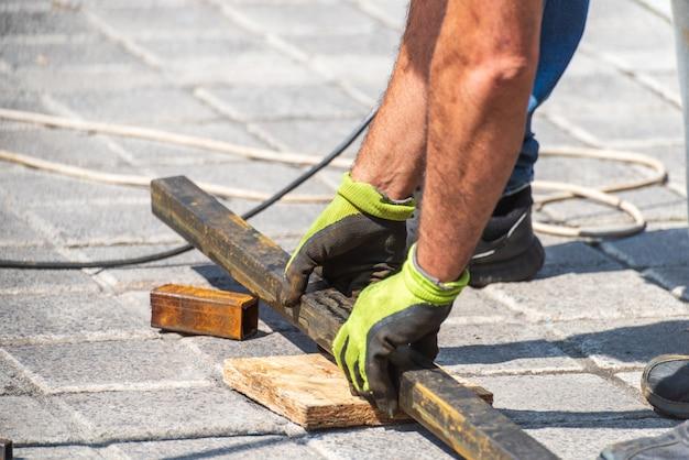 Mani che lavorano posano un tubo di metallo vicino a una costruzione Foto Premium
