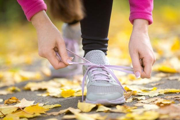 Mani che legano i calzoni dei formatori all'aperto di autunno Foto Gratuite
