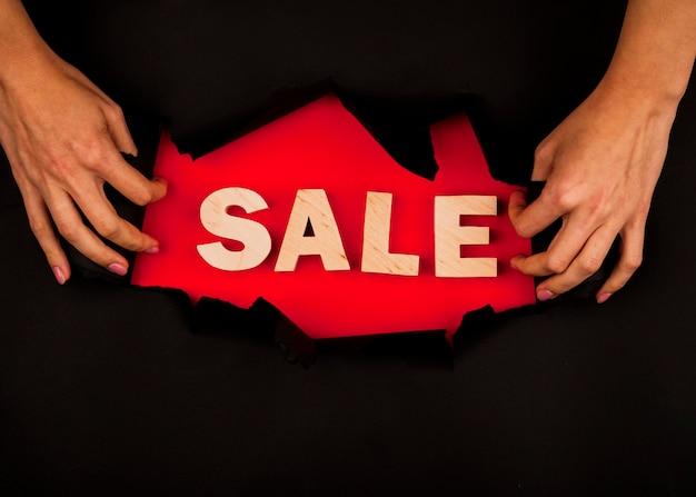 Mani che mostrano la parola di vendita attraverso la carta nera Foto Gratuite