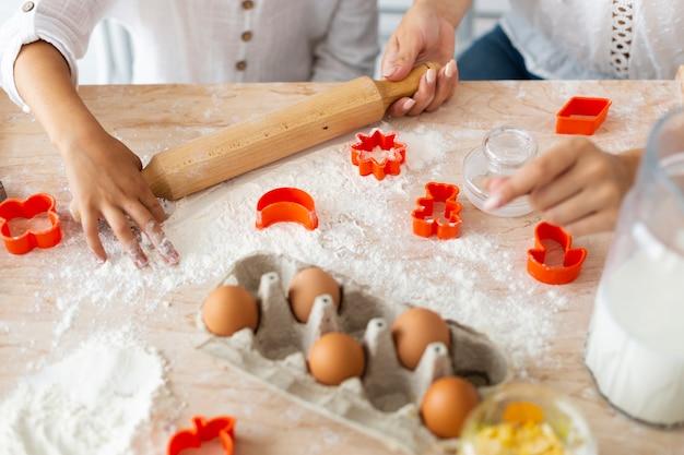 Mani che preparano i biscotti con il rullo della cucina Foto Gratuite
