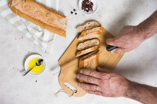 Mani che tagliano pagnotte di pane Foto Gratuite