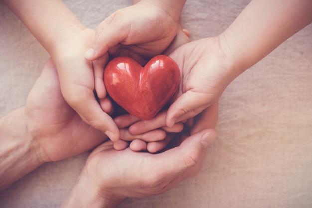 Mani che tengono cuore rosso Foto Premium