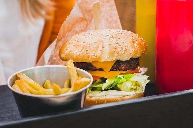 Mani che tengono fresco delizioso hamburger con patatine fritte sul tavolo in legno nero Foto Premium