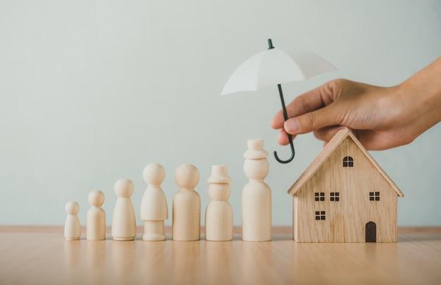 Mani che tengono gli ombrelli sui burattini, sulla famiglia e sulla casa di legno. concetto di cura della famiglia custode della famiglia mani che tengono ombrelli su marionette, famiglia e casa in legno. Foto Premium