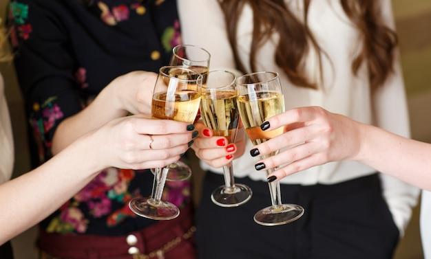 Mani che tengono i bicchieri di champagne facendo un brindisi Foto Premium