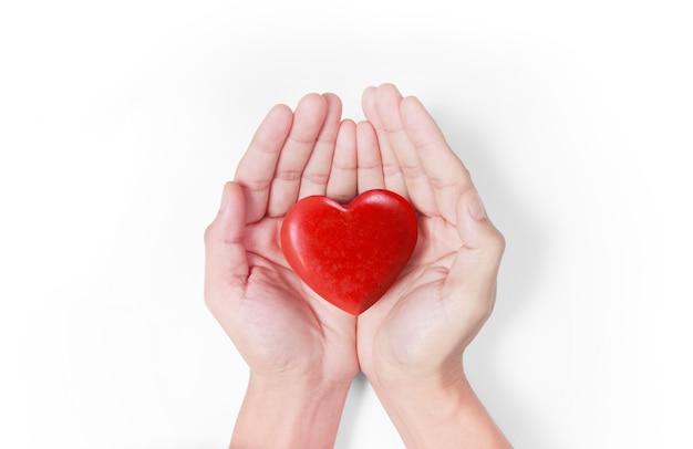Mani che tengono i concetti di cuore rosso, salute del cuore e donazione Foto Premium