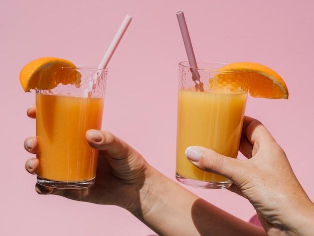 Mani che tengono i vetri con la vista frontale del succo d'arancia naturale Foto Gratuite