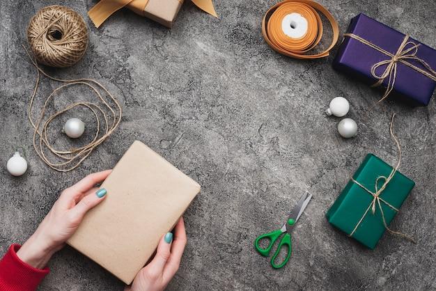 Mani che tengono il contenitore di regalo di natale con corda e le forbici Foto Gratuite