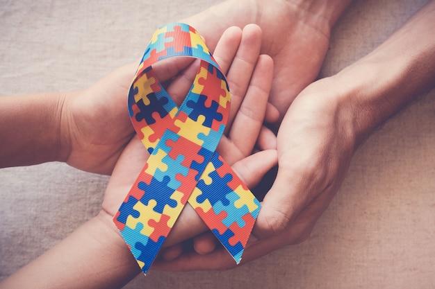 Mani che tengono il nastro del puzzle per la consapevolezza dell'autismo Foto Premium