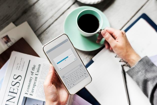 Mani che tengono il telefono cellulare di download con la bevanda della tazza di caffè Foto Gratuite