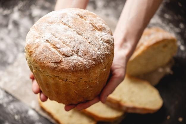 Mani che tengono in casa pane fresco naturale con una crosta dorata su un vecchio legno. cuocere prodotti da forno Foto Premium