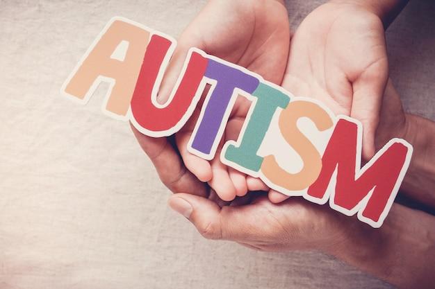 Mani che tengono la parola autismo, concetto di salute mentale, giornata mondiale di sensibilizzazione sull'autismo Foto Premium