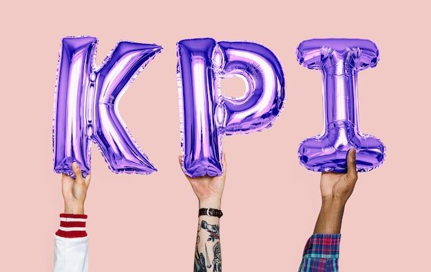 Mani che tengono la parola kpi in lettere a palloncino Foto Premium