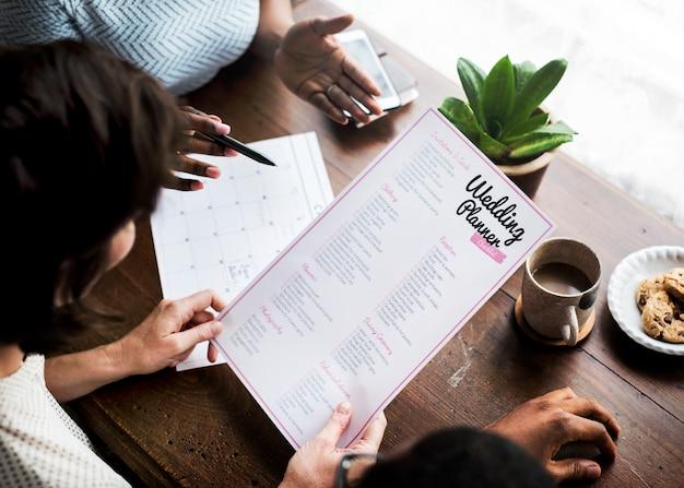 Mani che tengono la preparazione di informazioni della lista di controllo del pianificatore di nozze Foto Premium