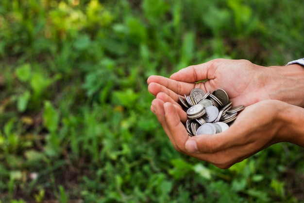 Mani che tengono le monete di risparmio all'aperto Foto Gratuite