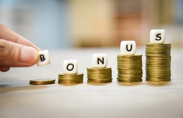 Mani che tengono le parole di bonus sulla pila monete scala Foto Premium
