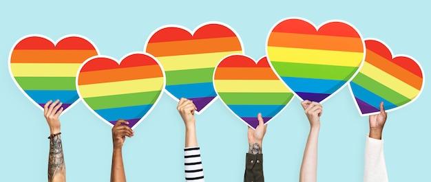 Mani che tengono un grafico del cuore dell'arcobaleno del lgbt Foto Premium