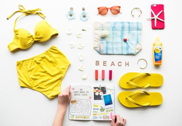 Mani che tengono una collezione di diario e spiaggia Foto Premium