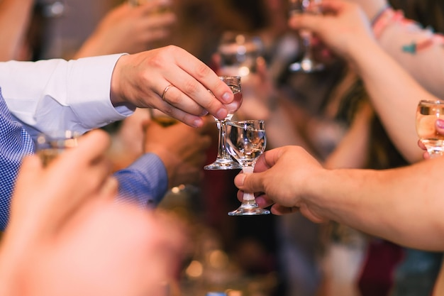 Mani con bicchieri di vodka che celebrano la tradizionale festa russa Foto Premium