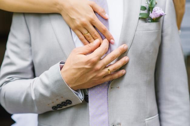 Mani con le fedi nuziali primo piano della sposa e dello sposo. un uomo tiene la mano della sposa Foto Premium