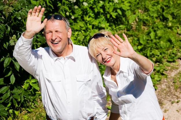 Mani d'ondeggiamento all'aperto felici delle coppie senior Foto Premium