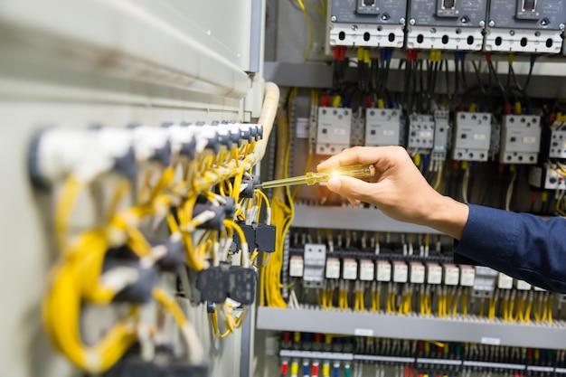 Mani degli elettricisti che verificano corrente elettrica nel pannello di controllo. Foto Premium