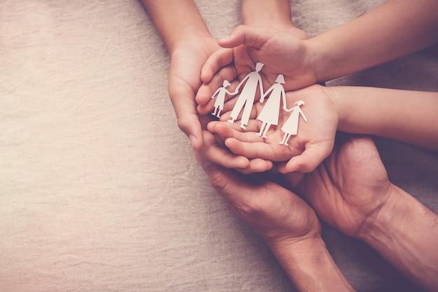 Mani dei bambini e dell'adulto che tengono il ritaglio di carta della famiglia Foto Premium