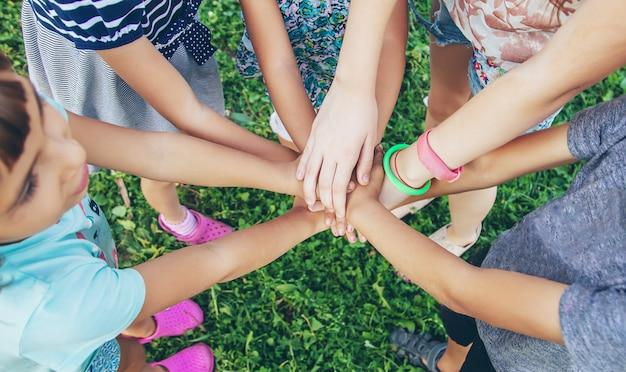 Mani dei bambini insieme su uno sfondo di erba. Foto Premium