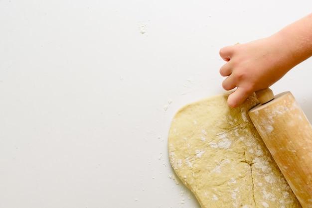 Mani del bambino che impastano una pizza con il mattarello. Foto Premium