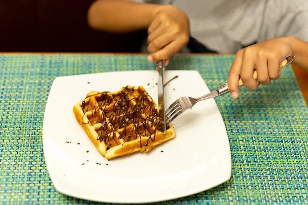 Mani del bambino che tagliano la cialda con coltello e forchetta Foto Premium