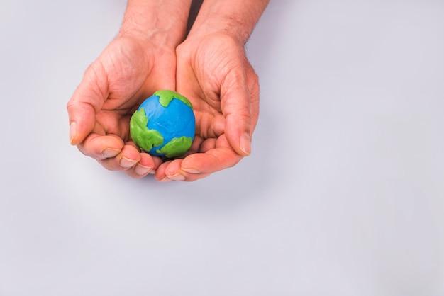 Mani del bambino che tiene il modello di argilla colorata del pianeta terra Foto Gratuite