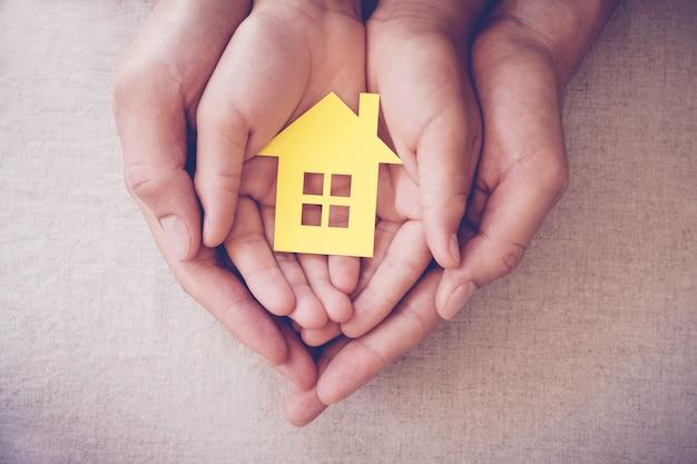 Mani del bambino e dell'adulto che tengono concetto giallo del riparo della casa, della casa di famiglia e del senzatetto Foto Premium