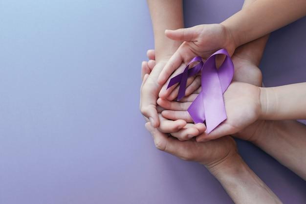 Mani del bambino e dell'adulto che tengono i nastri viola Foto Premium