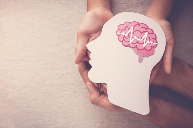 Mani del bambino e dell'adulto che tengono il ritaglio di carta del cervello di encefalografia, consapevolezza di epilessia e alzheimer, disturbo convulsivo, concetto di salute mentale Foto Premium