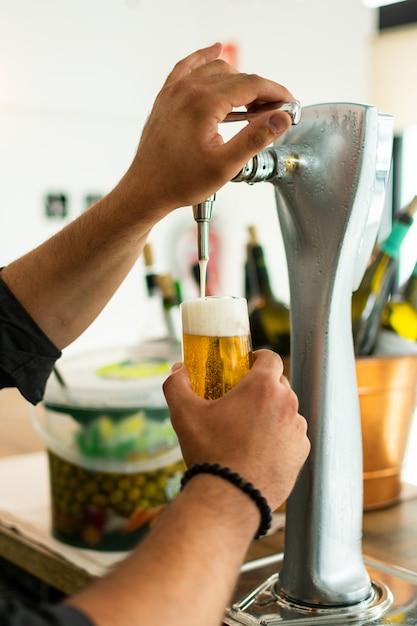 Mani del barista al rubinetto della birra che versa una birra alla spina alla spina che serve in un ristorante o in un pub. Foto Premium