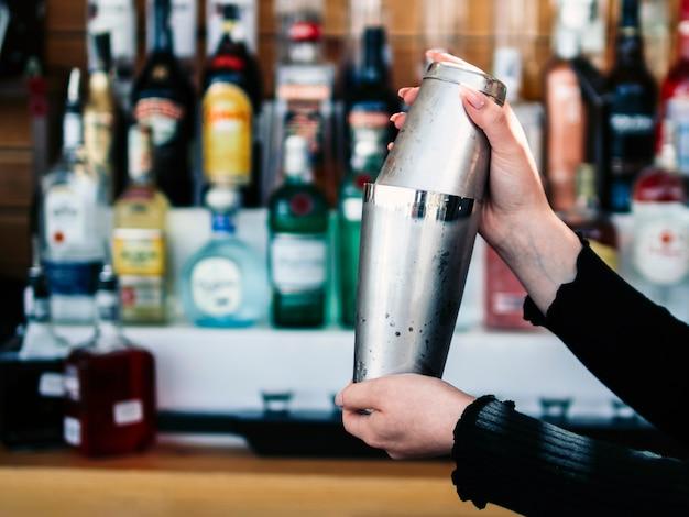 Mani del barista ritagliare la preparazione di bevande in shaker Foto Gratuite