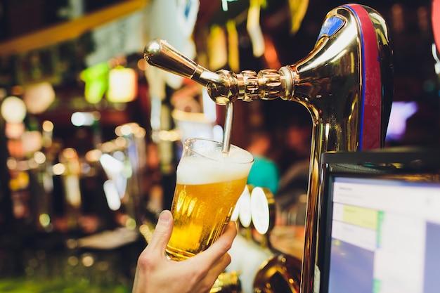 Mani del barista versando una birra chiara in un bicchiere. Foto Premium