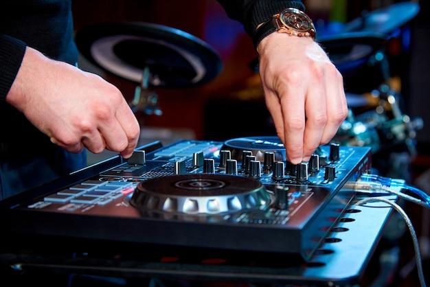 Mani del dj dietro il pannello di controllo sullo sfondo del set di batteria Foto Premium