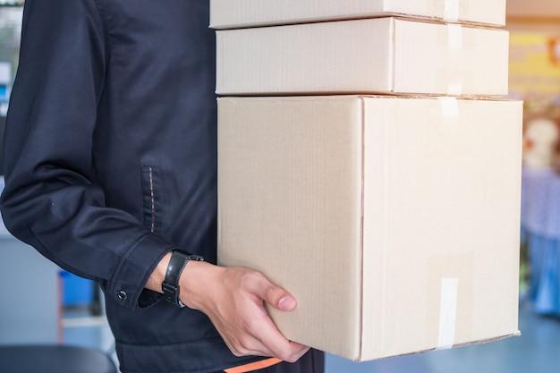 Mani del fattorino che tengono le scatole del pacchetto Foto Premium