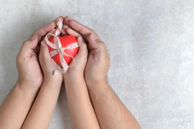 Mani del padre e del bambino che tengono cuore rosso Foto Premium