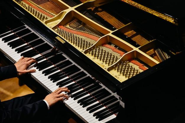 Mani del pianista classico che suonano il suo pianoforte durante un concerto. Foto Premium