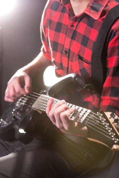 Mani del primo piano di giovane chitarrista con la chitarra elettrica. Foto Premium