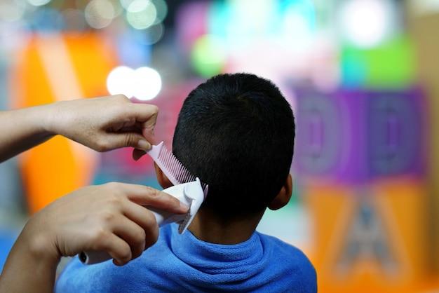 Mani del ragazzino dei capelli di taglio del parrucchiere che utilizza pettine e tagliatore nel bello parrucchiere. Foto Premium