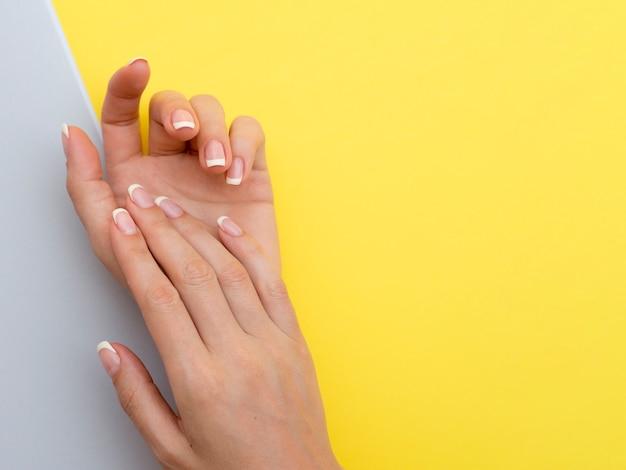 Mani delicate della donna con lo spazio giallo della copia Foto Gratuite