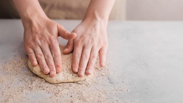 Mani dell'angolo alto che producono pane Foto Gratuite